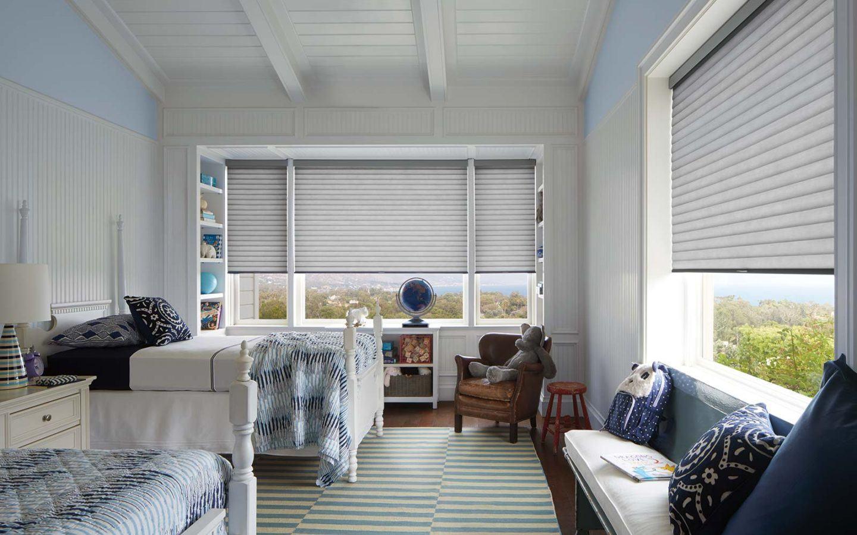 a bedroom with Hunter Douglas cellular honeycomb sonette blinds