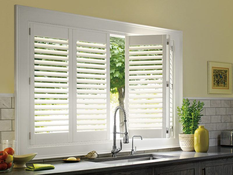 Hunter Douglas white shutters behind a kitchen sink