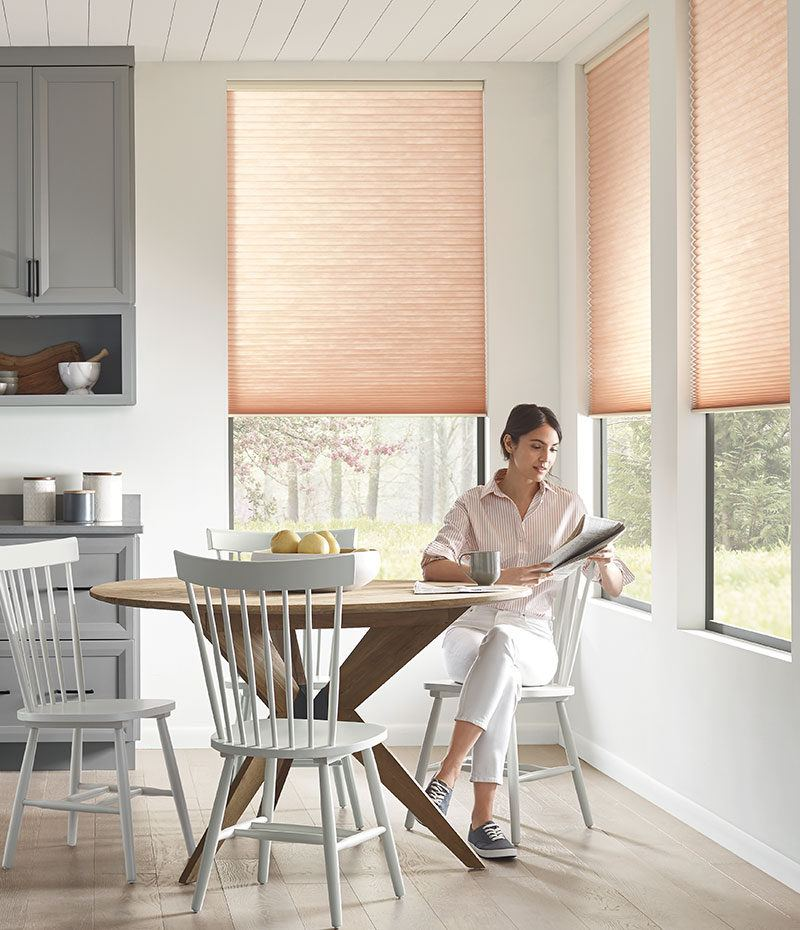 a woman sitting in her kitchen reading a newspaper with Hunter Douglas blinds covering the windows behind her