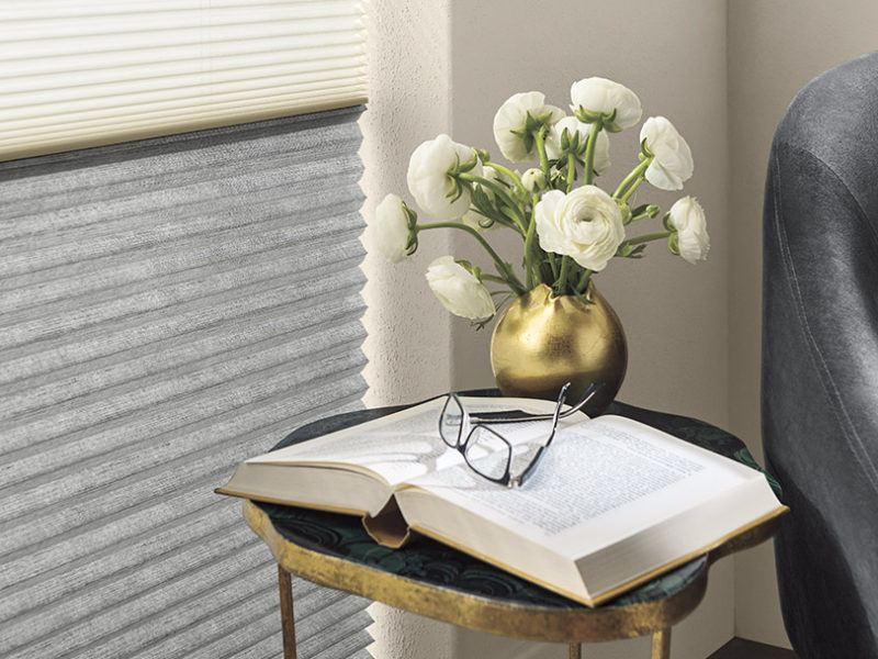 Hunter Douglas cellular shades being featured next to an open book with glasses