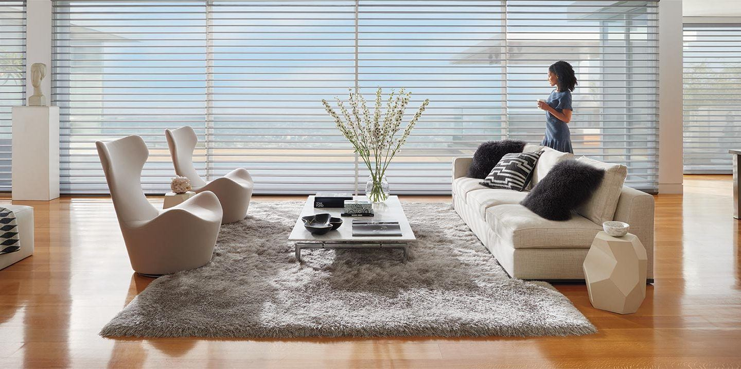 woman standing next to horizontal blinds in her living room