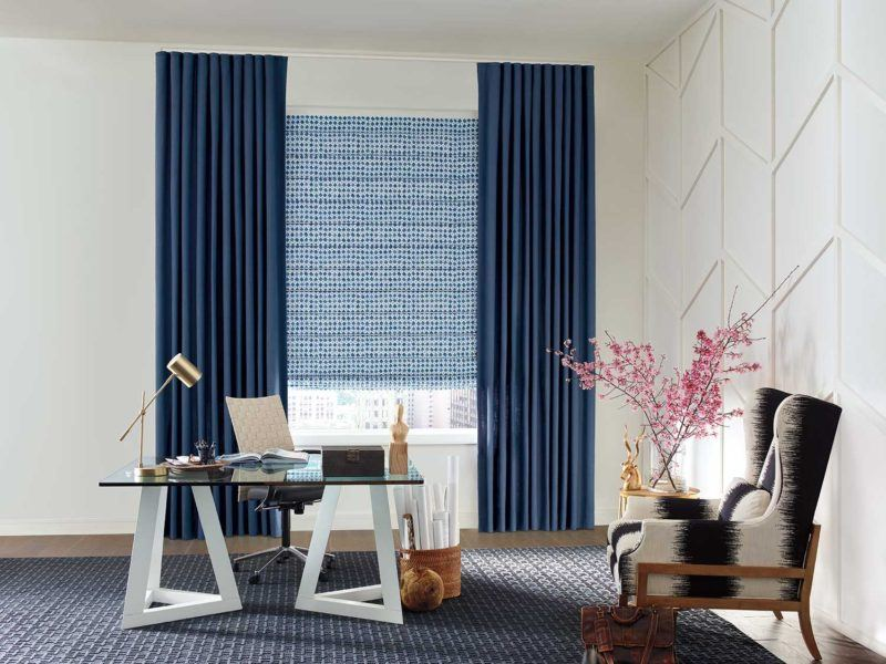 a desk in the middle of an office with floor length blue drapery and a Hunter Douglas blind covering the window