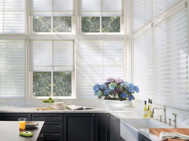 a kitchen with large windows that have Hunter Douglas motorized white blinds