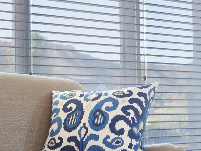 Hunter Douglas silhouette blinds behind a couch with a blue accent pillow