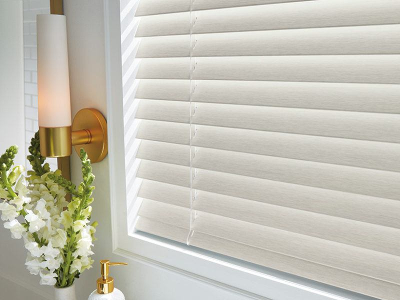 Close up photo of white cord-lock faux wood blinds