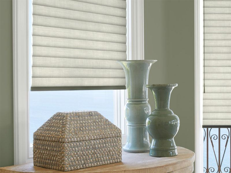 Hunter Douglas Sonnette soft touch blinds featured behind two blue vases and a decorative box
