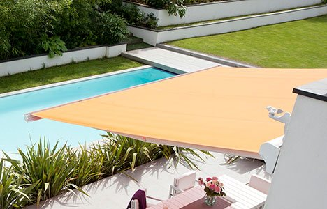 a retractable yellow awning covering a patio in a backyard with a pool