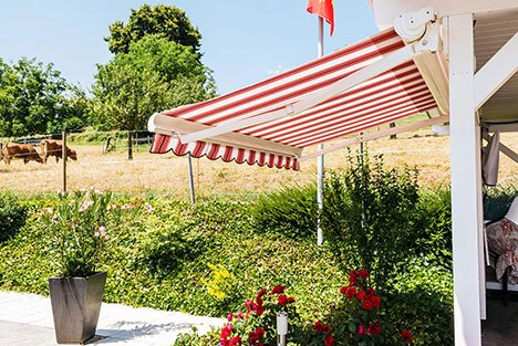 a patio with a retractable red striped awning