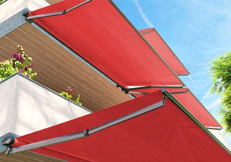 an outdoor patio covered by bright red retractable awnings