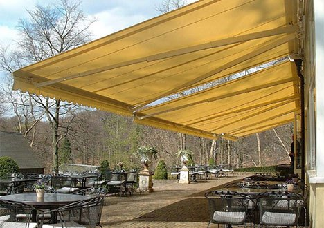 a patio with several empty tables, being covered in shade from three retractable awnings