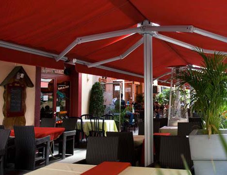 a restaurant patio being covered by large, red, stand alone awnings