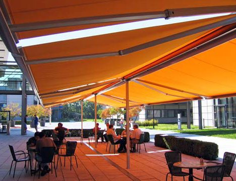 a patio being covered in shade by large yellow stand alone awnings