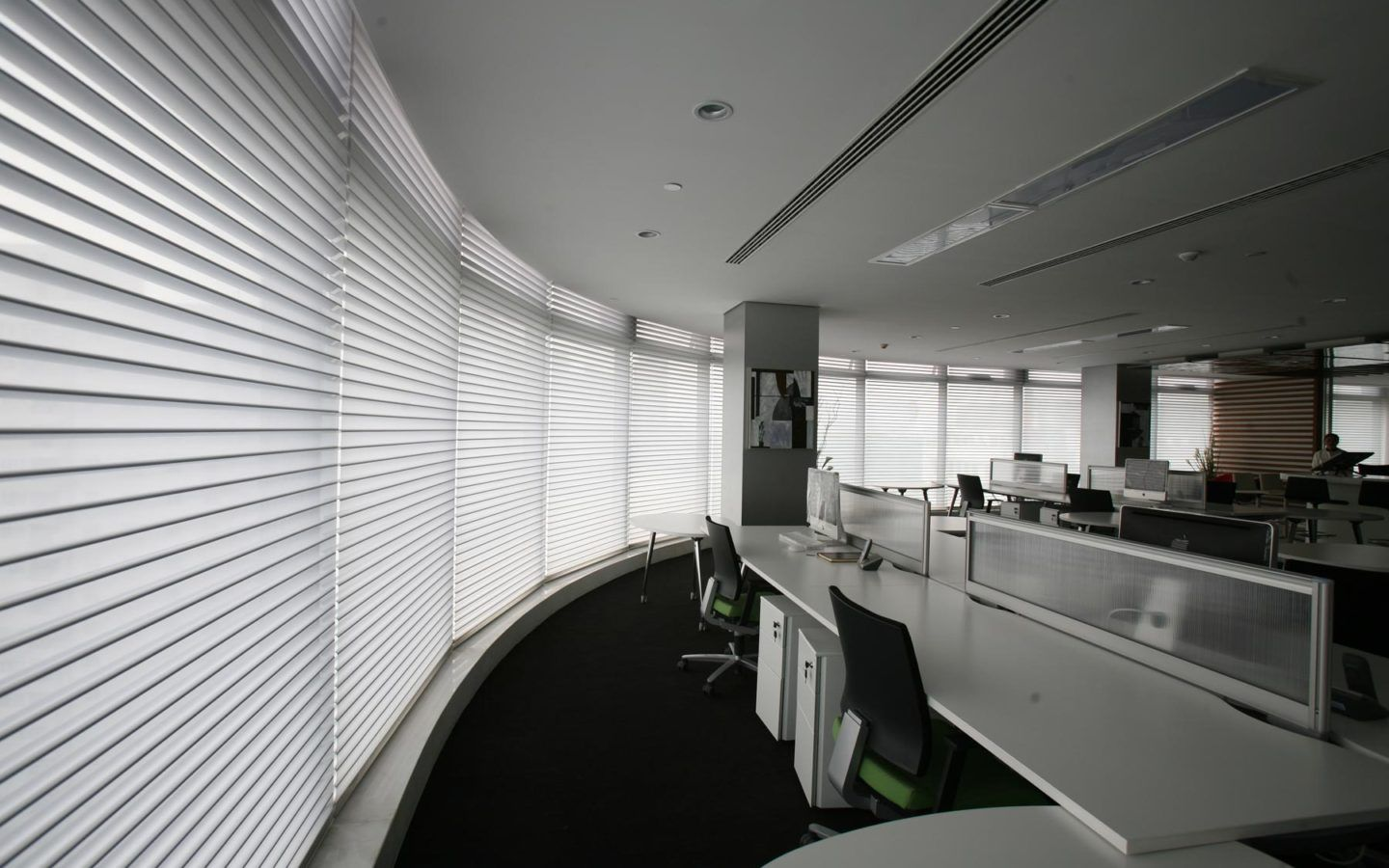 the interior of a commercial office with large windows with horizontal blinds