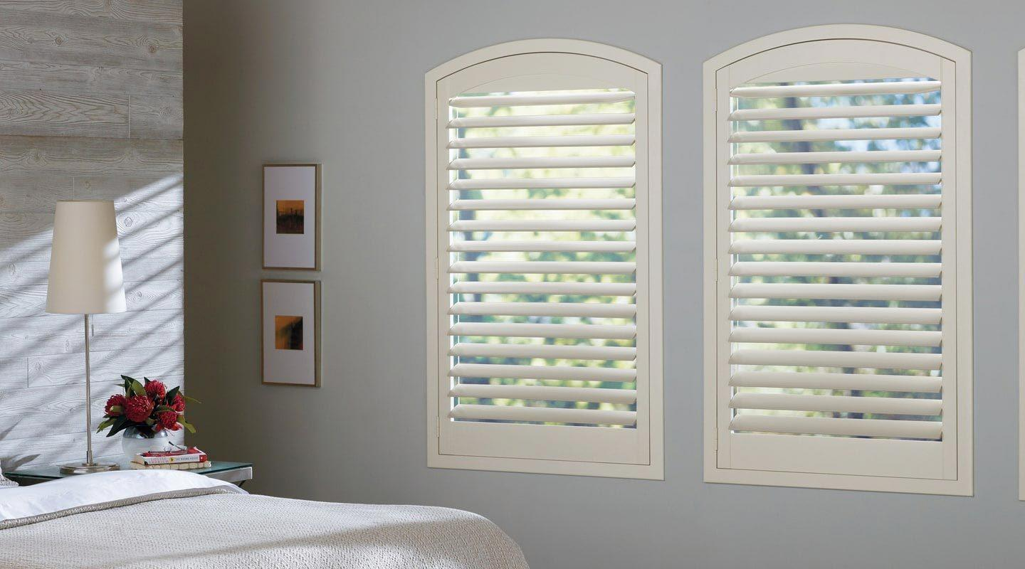 a bedroom featuring Hunter Douglas new style shutters