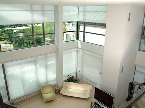 A large living room with high ceilings featuring motorized blinds