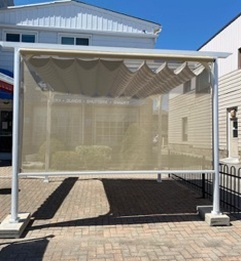 a patio cover outside of the Sunshade Blinds and Drapery storefront in Ajax
