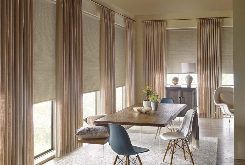 a dining room with floor to ceiling Hunter Douglas Drapery